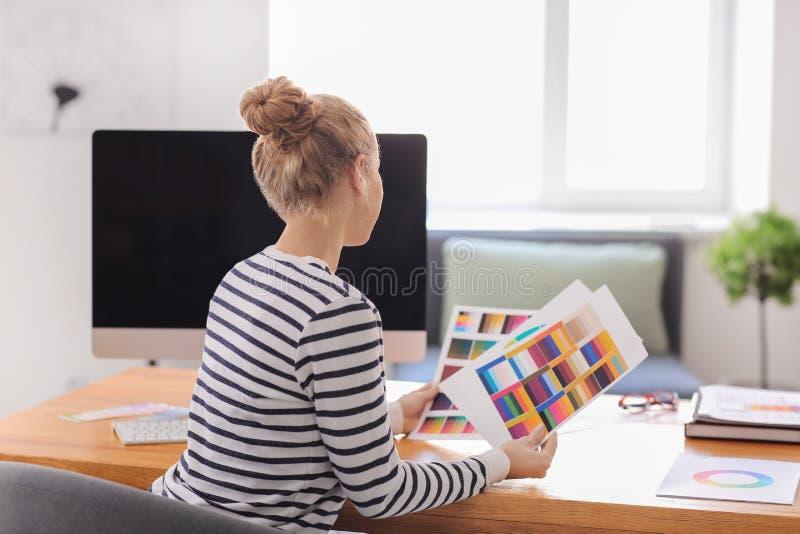 Bello giovane progettista che lavora con la tavolozza di colore in ufficio immagini stock