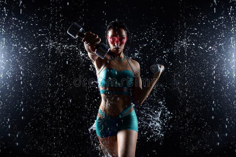 Bello giovane ragazza in posa di abbigliamento sportivo con stupidaggini in aqua studio Le gocce d'acqua si sono diffuse sul suo  fotografia stock