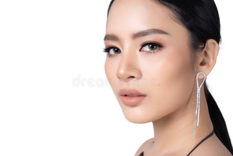 Bellissima giovane donna asiatica ritratto con un trucco perfetto Isolamento di gioielli del modello di moda su fondo bianco Stud immagine stock