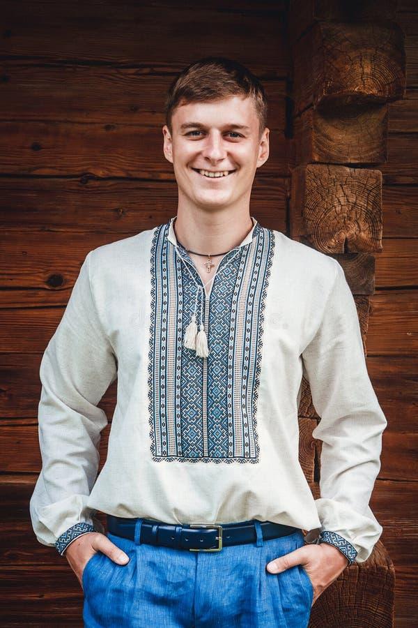 Bello giovane tipo in una camicia ricamata sui precedenti di una casa di legno fotografie stock libere da diritti