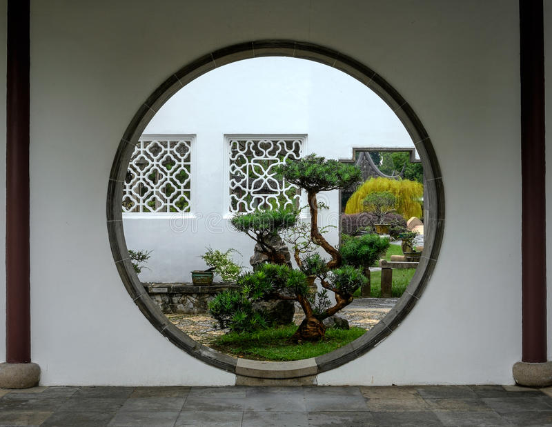 Bello grande albero dei bonsai attraverso l'entrata del cerchio al giardino immagini stock