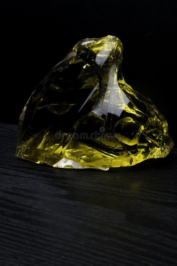 Bello grande pezzo di ambra su un fondo nero Pietra di Sun La resina petrificata è un materiale di cristallo naturale per gioiell fotografie stock libere da diritti