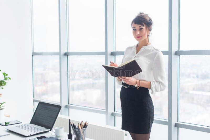 Bello impiegato femminile che sta nell'ufficio nel suo luogo di lavoro, tenendo pianificatore, leggente orario per il giorno, vis immagini stock