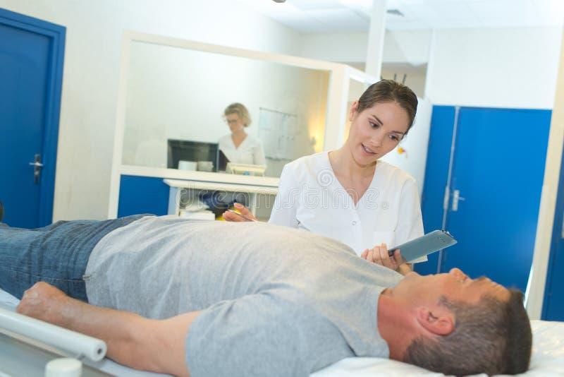 Bello infermiere che visita paziente maturo che risiede nel letto di ospedale fotografia stock libera da diritti