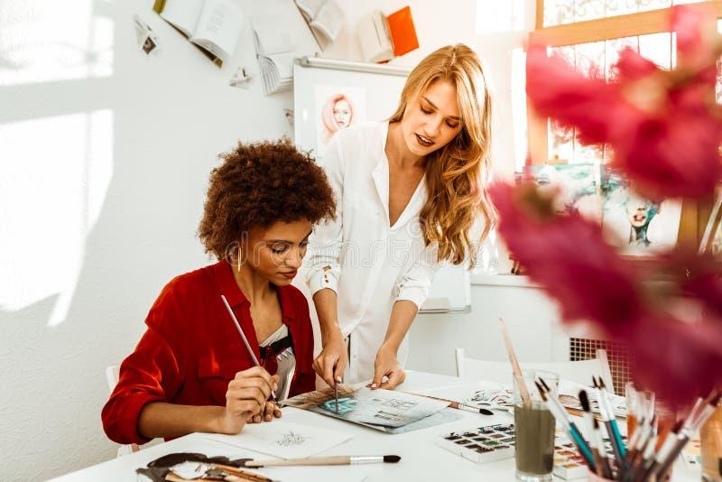 Bello insegnante di arte bionda-dai capelli alla moda che aiuta il suo studente fotografia stock