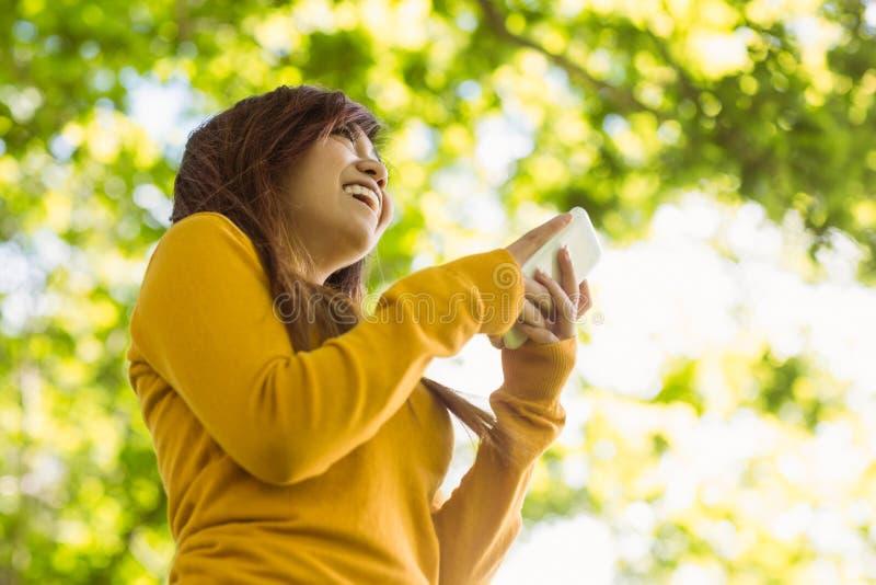 Bello invio di messaggi di testo della giovane donna in parco immagini stock