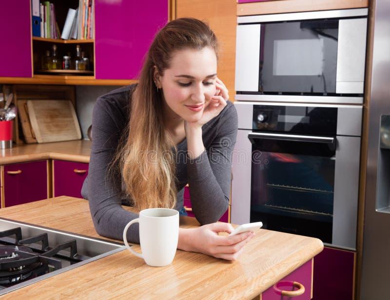 Bello invio di messaggi di testo sereno della giovane donna sopra un fondo della cucina fotografia stock libera da diritti