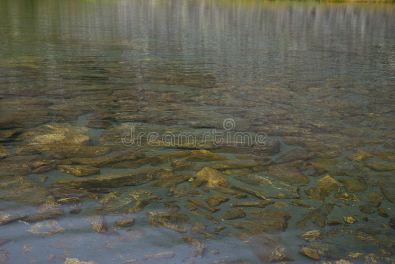 Bello lago della montagna circondato dalle montagne impressionanti fotografia stock