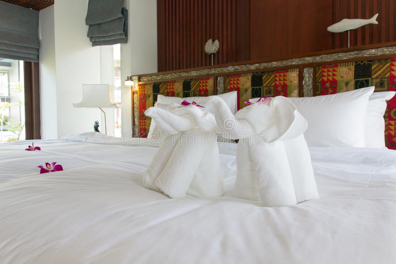 Bello letto appena fatto con l'asciugamano dell'elefante nei tropici immagini stock
