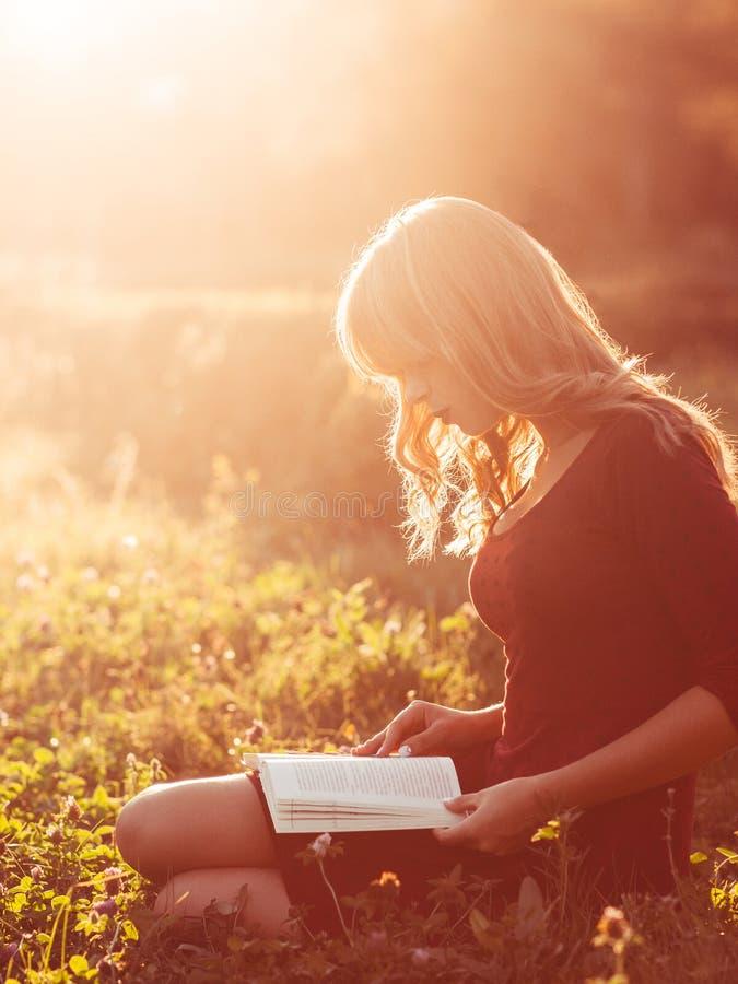 Bello libro di lettura della donna in natura, chiarore del sole fotografia stock libera da diritti