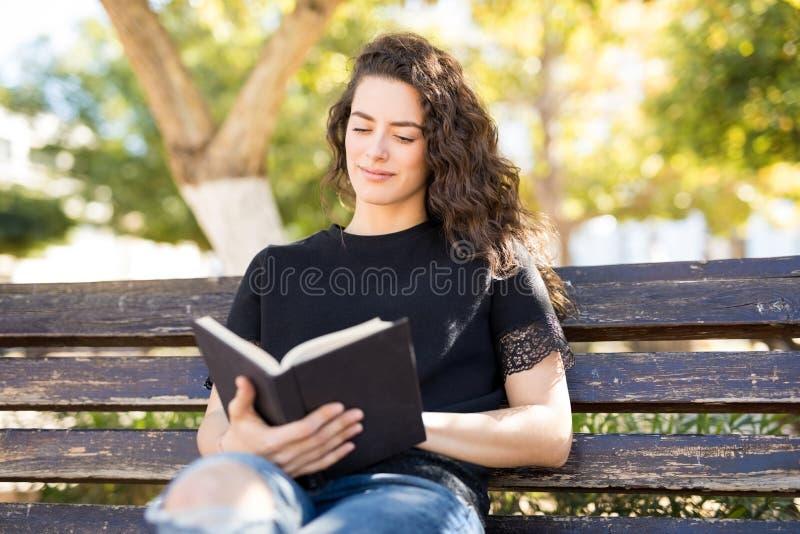 Bello libro di lettura della donna in sosta immagini stock libere da diritti