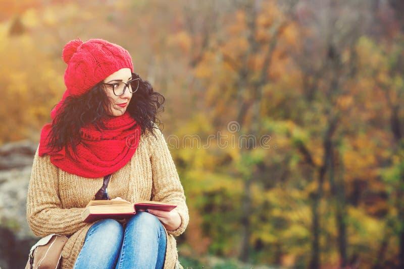 Bello libro di lettura della giovane donna in un parco e nel godere del tempo soleggiato Concetto di autunno e di stile di vita fotografie stock