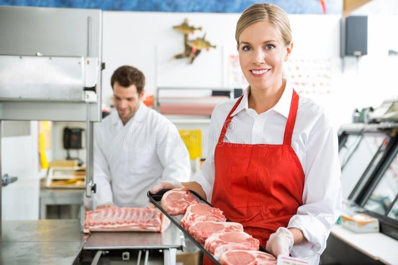 Bello macellaio Holding Meat Tray In Store immagini stock libere da diritti