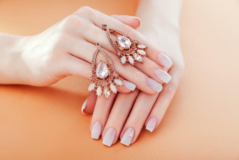 Bello manicure del ombre con gli orecchini Progettazione francese del chiodo Gioielli della tenuta della donna Concetto di modo immagine stock libera da diritti