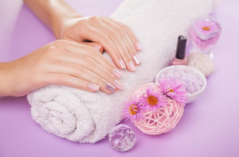 Bello manicure rosa e d'argento con i fiori e gli elementi essenziali della stazione termale fotografia stock