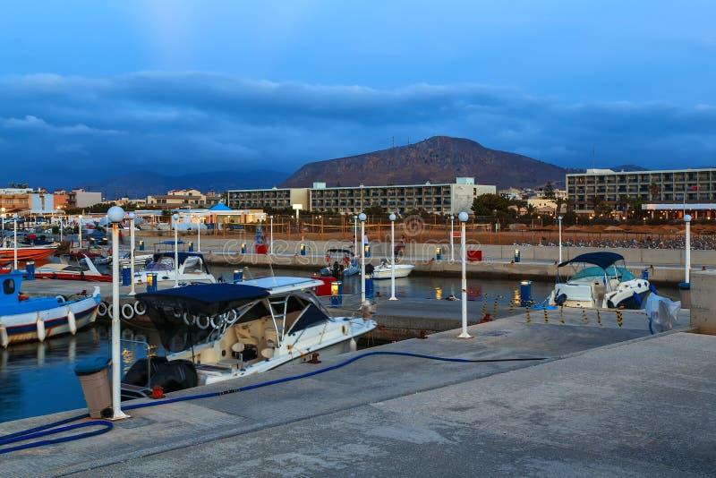 Bello mare con la luce morbida di sera del tramonto contro il cielo nuvoloso con la linea costiera stazione turistica, su Creta L fotografie stock