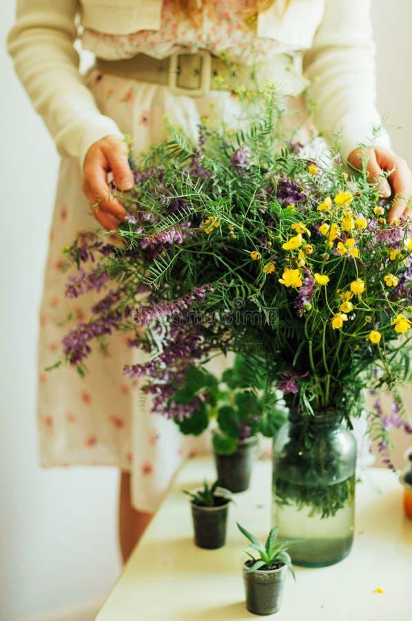 Bello mazzo dei wildflowers porpora e gialli nella luce della stanza su una tavola bianca immagine stock libera da diritti