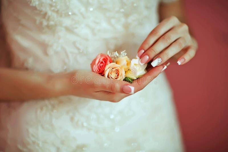 Bello mazzo delicato di nozze del fiore con le rose bianche e rosa nelle mani della sposa, mattina della sposa fotografie stock libere da diritti