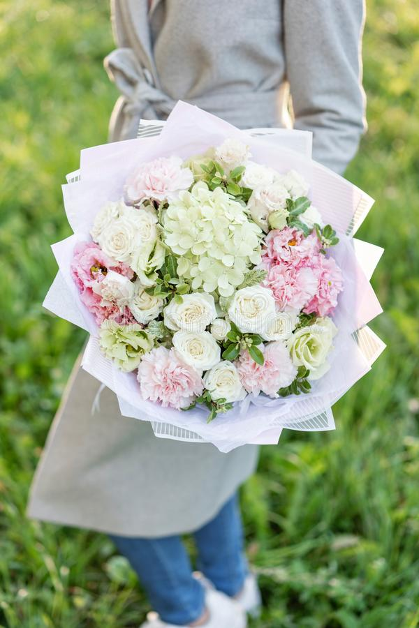 Bello mazzo della molla del primo piano in mani la disposizione dei fiori delicata con colore pastello rosa e verde fiorisce prat immagini stock