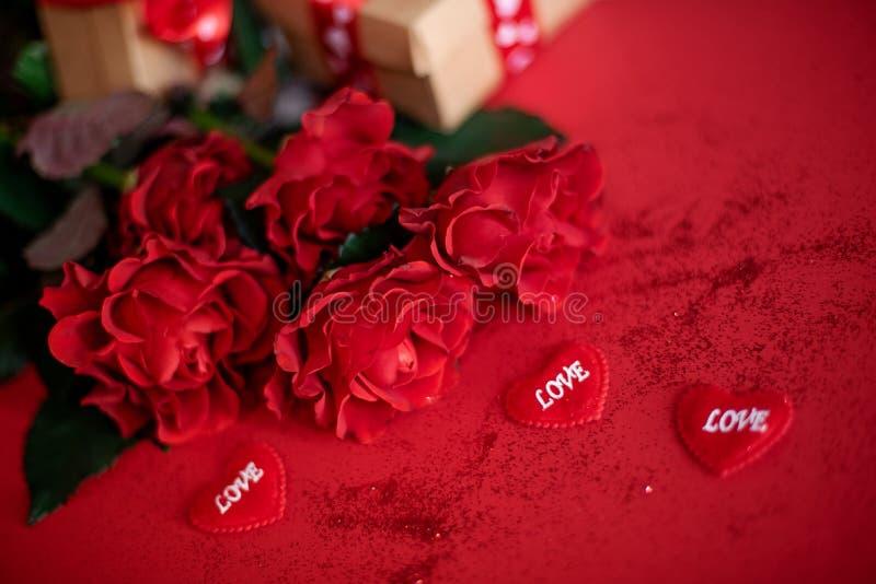 Bello mazzo delle rose con i contenitori di regalo su un fondo rosso immagini stock