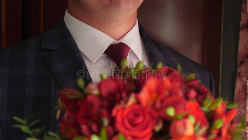 Bello mazzo delle rose rosse in mani degli uomini in rivestimento in un legame rosso ed in una camicia bianca Primo piano fotografie stock