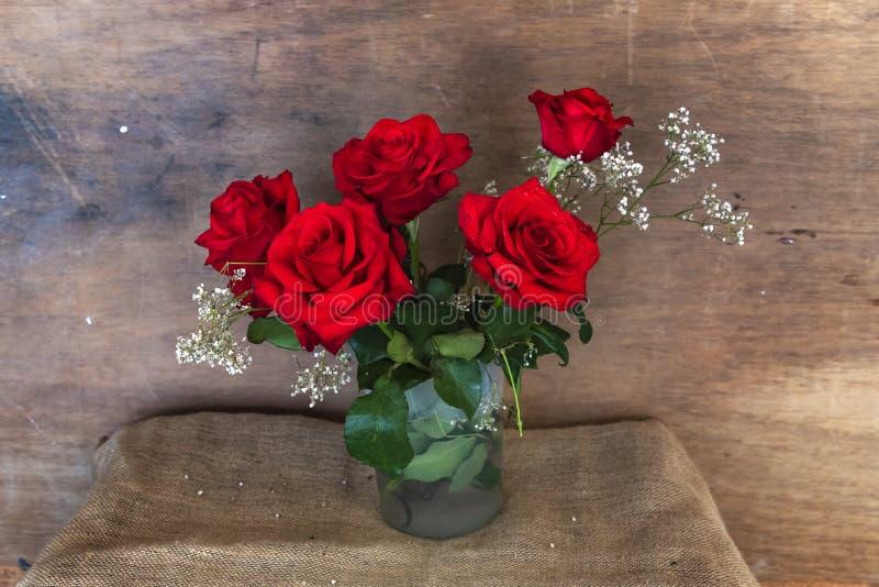Bello mazzo delle rose rosse su fondo rustico con lo spazio della copia immagini stock