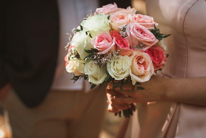 Bello mazzo di nozze delle rose crema in mani della sposa fotografia stock