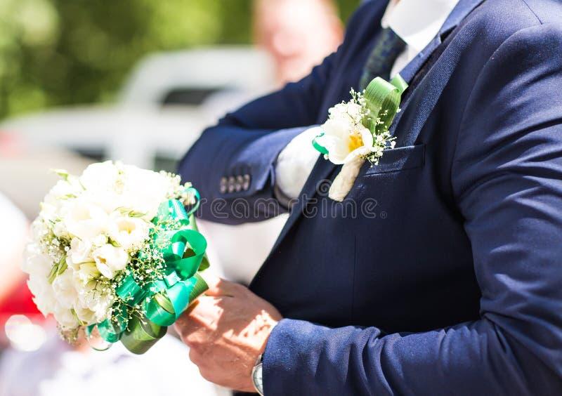 Bello mazzo di nozze in mani dello sposo Regalo alla sposa Vestito classico blu del progettista con l'occhiello immagini stock