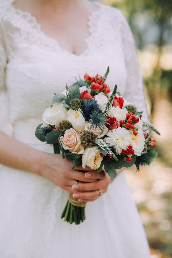 Bello mazzo elegante di nozze di autunno delle rose bianche e dei fiori rossi nelle mani della sposa in vestito da sposa bianco fotografia stock