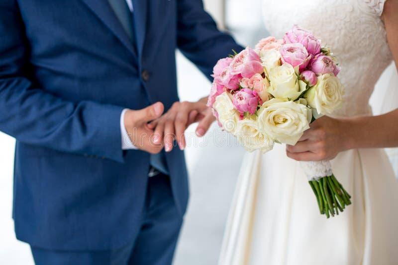Bello mazzo nuziale delicato delle rose e dei fiori bianchi e rosa in mani della sposa immagini stock