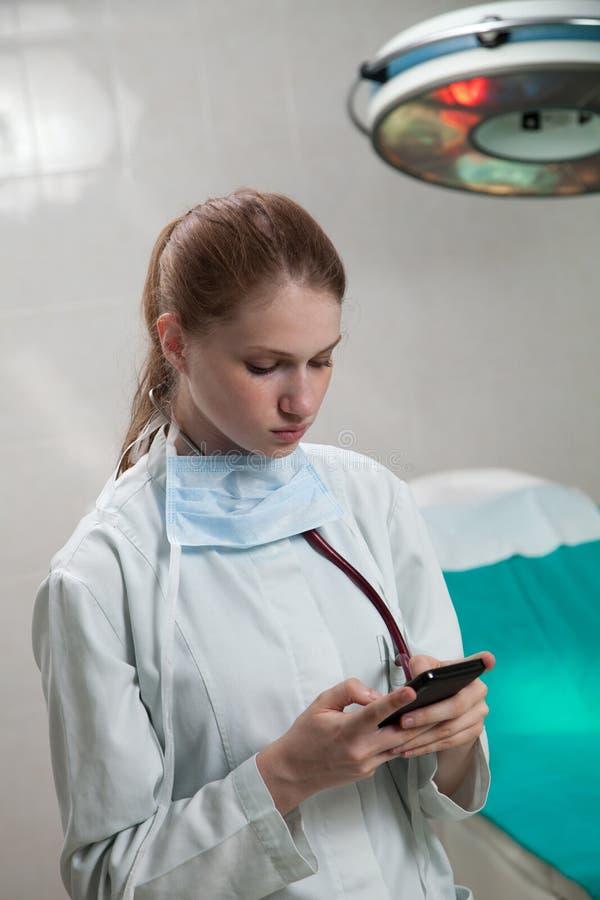 Bello medico che per mezzo di uno Smart Phone immagine stock
