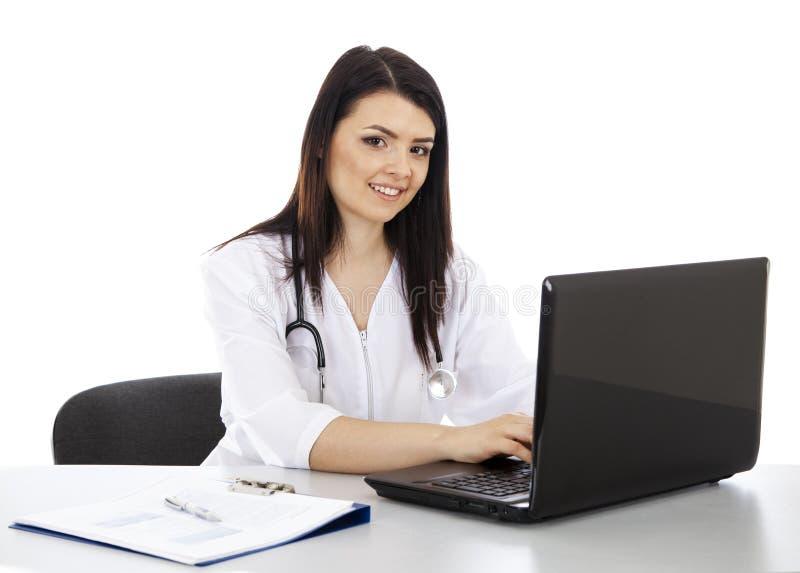 Bello medico della donna che lavora ad un computer portatile ed a sorridere immagine stock