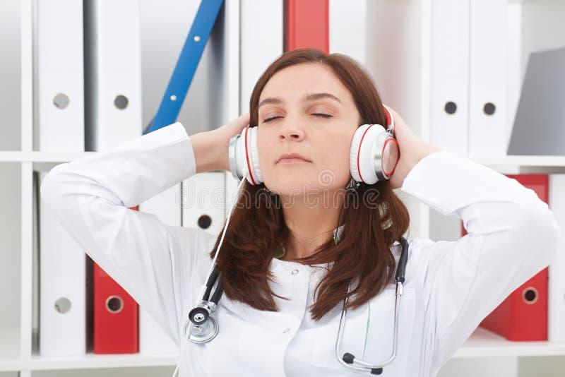 Bello medico femminile della medicina che gode della musica nel suo luogo di lavoro con gli occhi chiusi Medico rilassi il concet fotografia stock libera da diritti