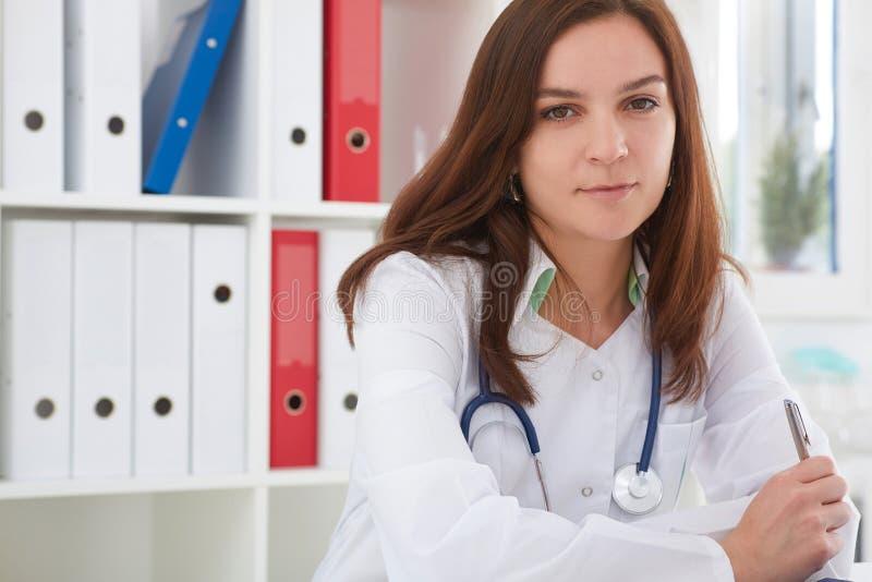 Bello medico femminile della medicina che si siede alla tavola e che tiene una penna Medico sta aspettando il paziente per esamin immagini stock libere da diritti