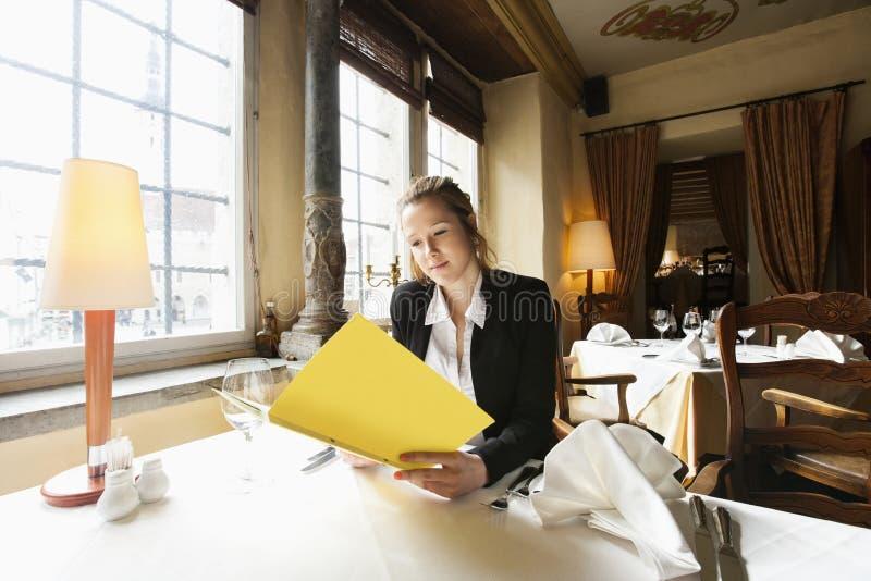 Bello menu della lettura del cliente alla tavola del ristorante fotografia stock libera da diritti