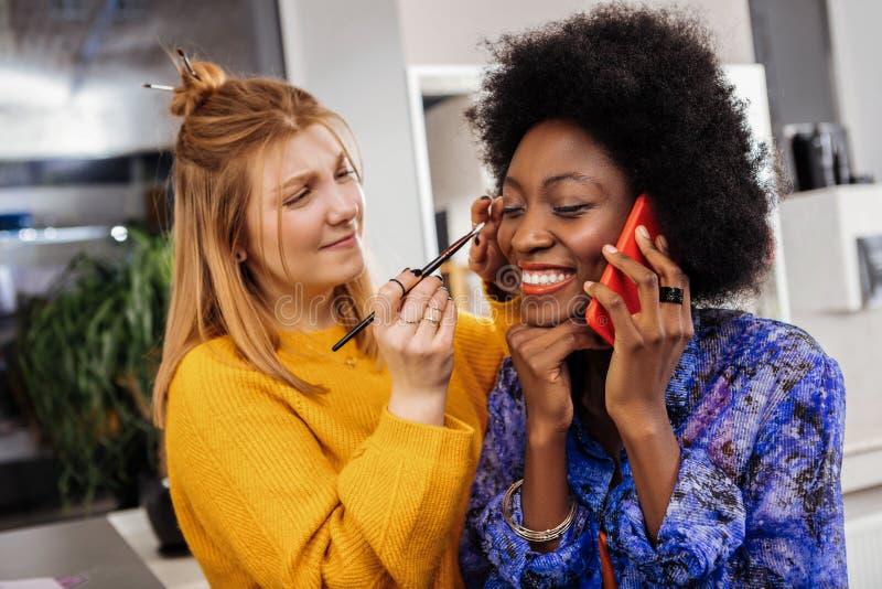 Bello modello afroamericano sorridente con la sensibilità di corallo del rossetto per favore fotografie stock libere da diritti