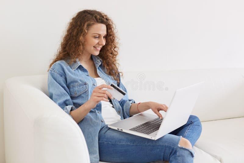 Bello modello allegro che posa sul sofà a casa, essendo occupato con le attività in tutto il computer portatile, servizi online d fotografia stock libera da diritti