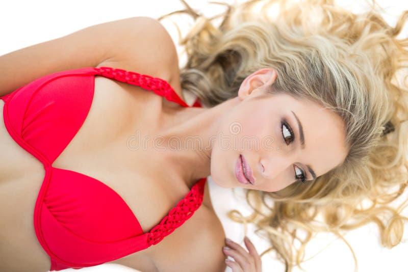 Bello modello biondo che indossa distogliere lo sguardo rosso del bikini fotografia stock