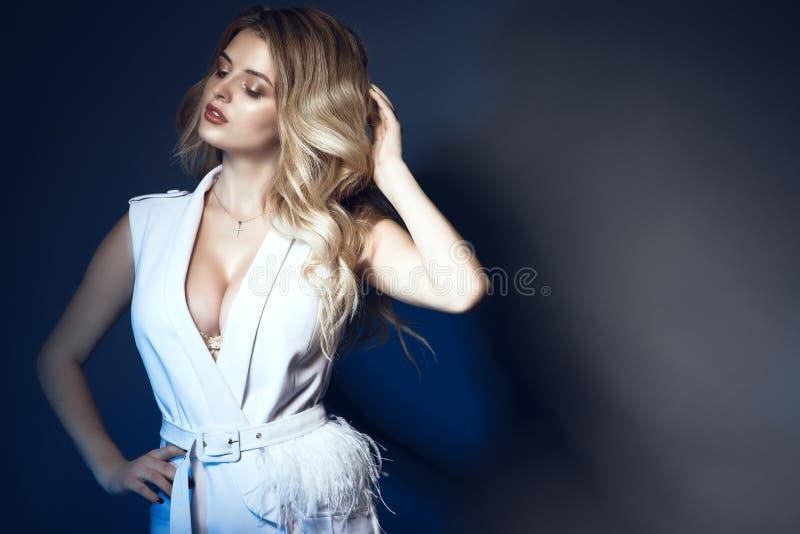 Bello modello biondo che porta vestito bianco alla moda con l'immersione della scollatura decorata con le piume che toccano i suo fotografia stock