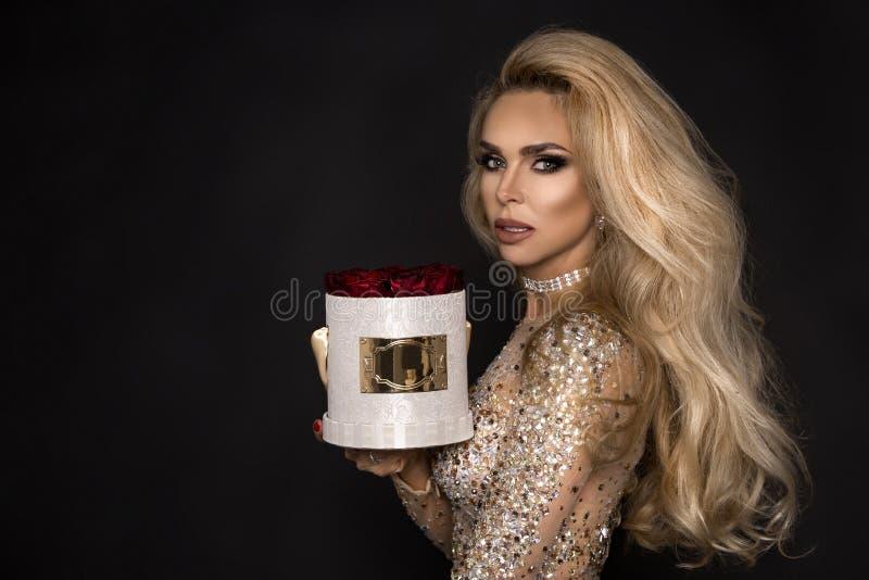 Bello modello biondo in vestito elegante che tiene un regalo, contenitore di fiore con le rose Regalo del `s del biglietto di S fotografia stock libera da diritti