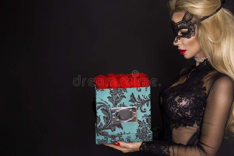 Bello modello biondo in vestito elegante che tiene un regalo, contenitore di fiore con le rose Regalo del `s del biglietto di S fotografie stock