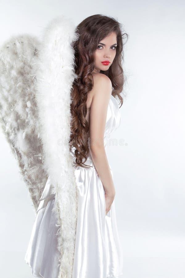 Bello modello castana di angelo della ragazza con le ali isolate su bianco immagine stock libera da diritti