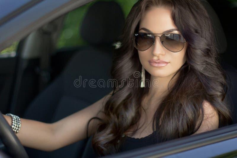 Bello modello castana sexy della donna con gli occhiali da sole che si siedono nella a fotografia stock