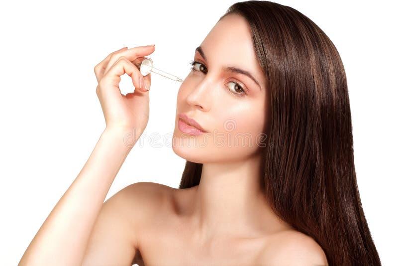 Bello modello che applica un trattamento cosmetico del siero della pelle immagine stock