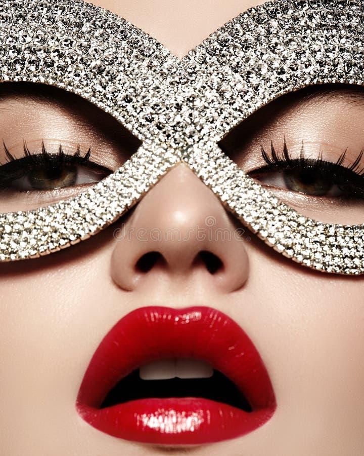 Bello modello con trucco delle labbra di modo che indossa maschera brillante luminosa Donna di stile di travestimento Sguardo di  fotografia stock