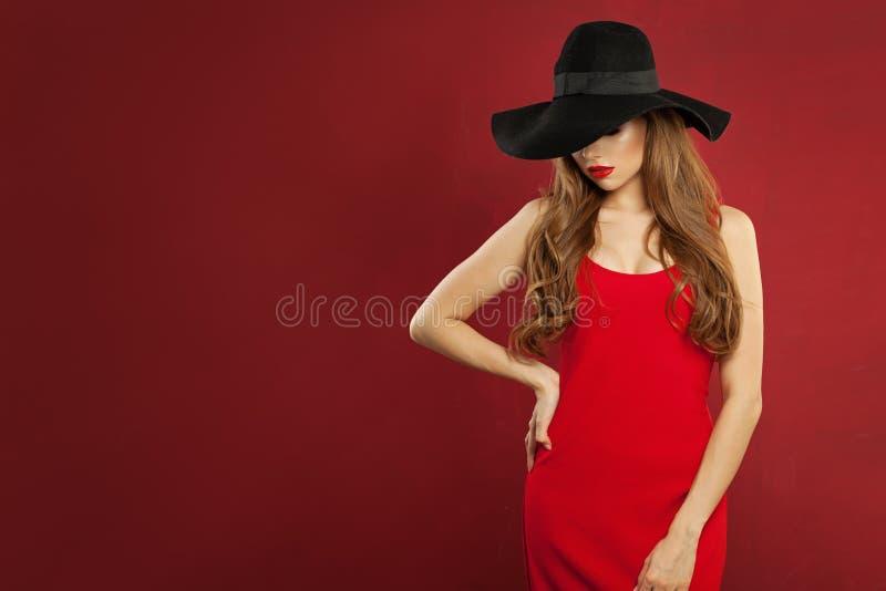 Bello modello di moda della donna che indossa vestito rosso e condizione black hat contro il fondo rosso della parete immagine stock