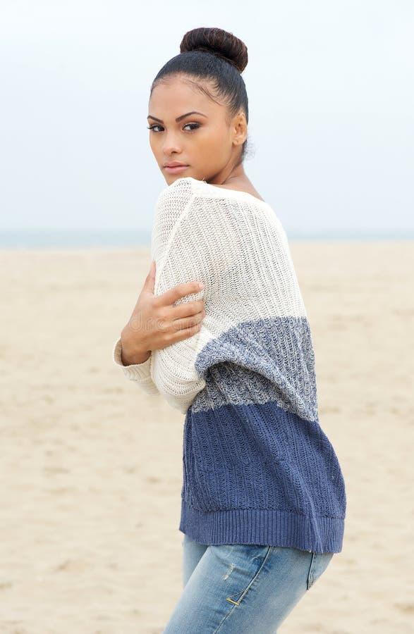 Bello modello di moda in maglione che sta alla spiaggia da solo immagine stock