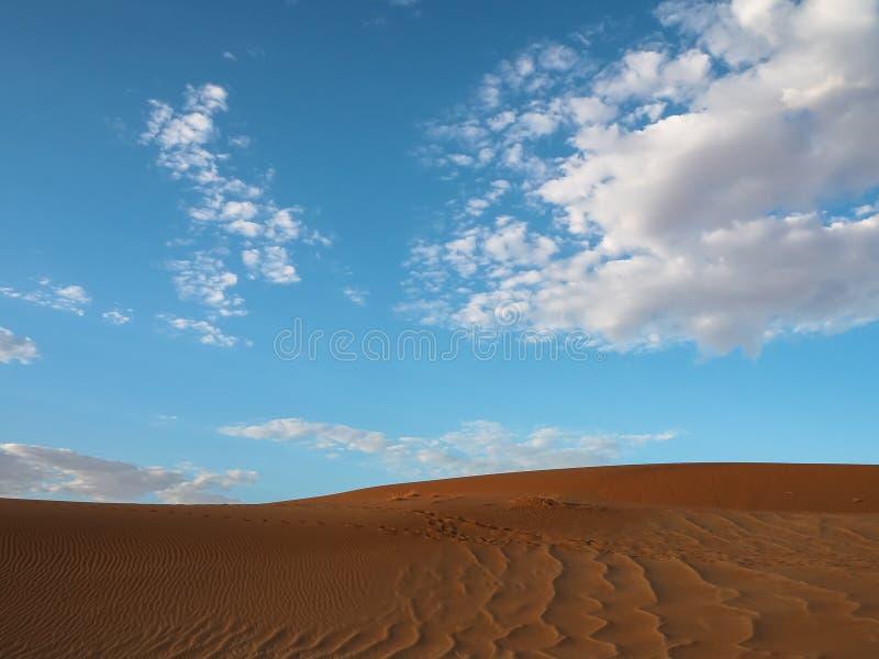 Bello modello naturale della duna di sabbia rossa arrugginita del deserto con cielo blu luminoso ed il fondo bianco della nuvola, fotografie stock libere da diritti