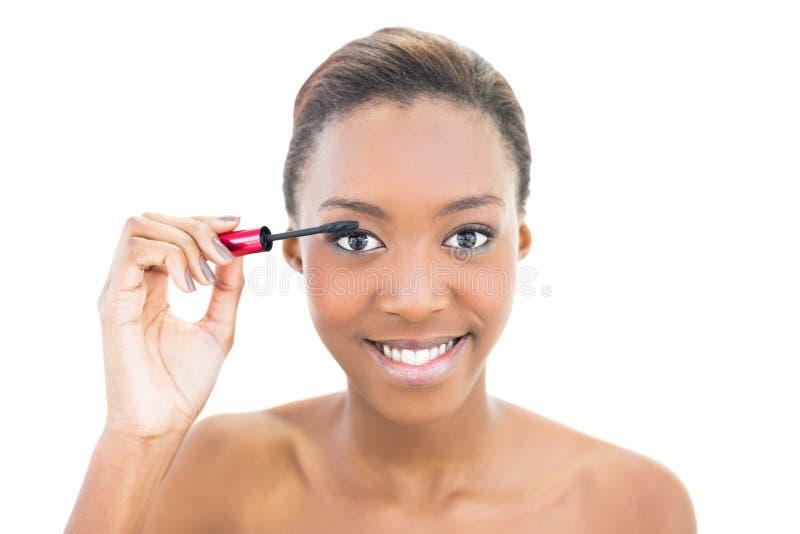 Bello modello sorridente che applica mascara fotografie stock libere da diritti