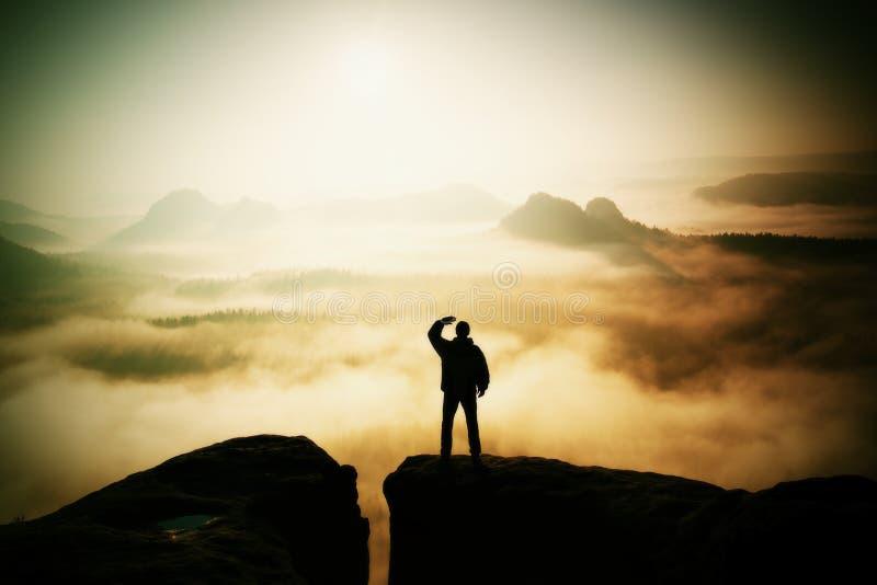 Bello momento il miracolo della natura L'uomo sta sul picco della roccia dell'arenaria in parco nazionale Sassonia Svizzera e gua immagine stock libera da diritti